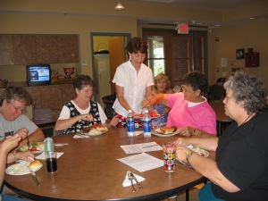 Julie, an HHH volunteer, helps serve guests dinner during their stay.