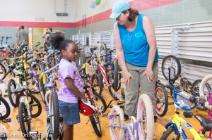 Volunteer assists a new rider select her bike at Hands On Nashville's ReCYCLE for Kids giveaway event at Kirkpatrick Community Center on May 17, 2015.