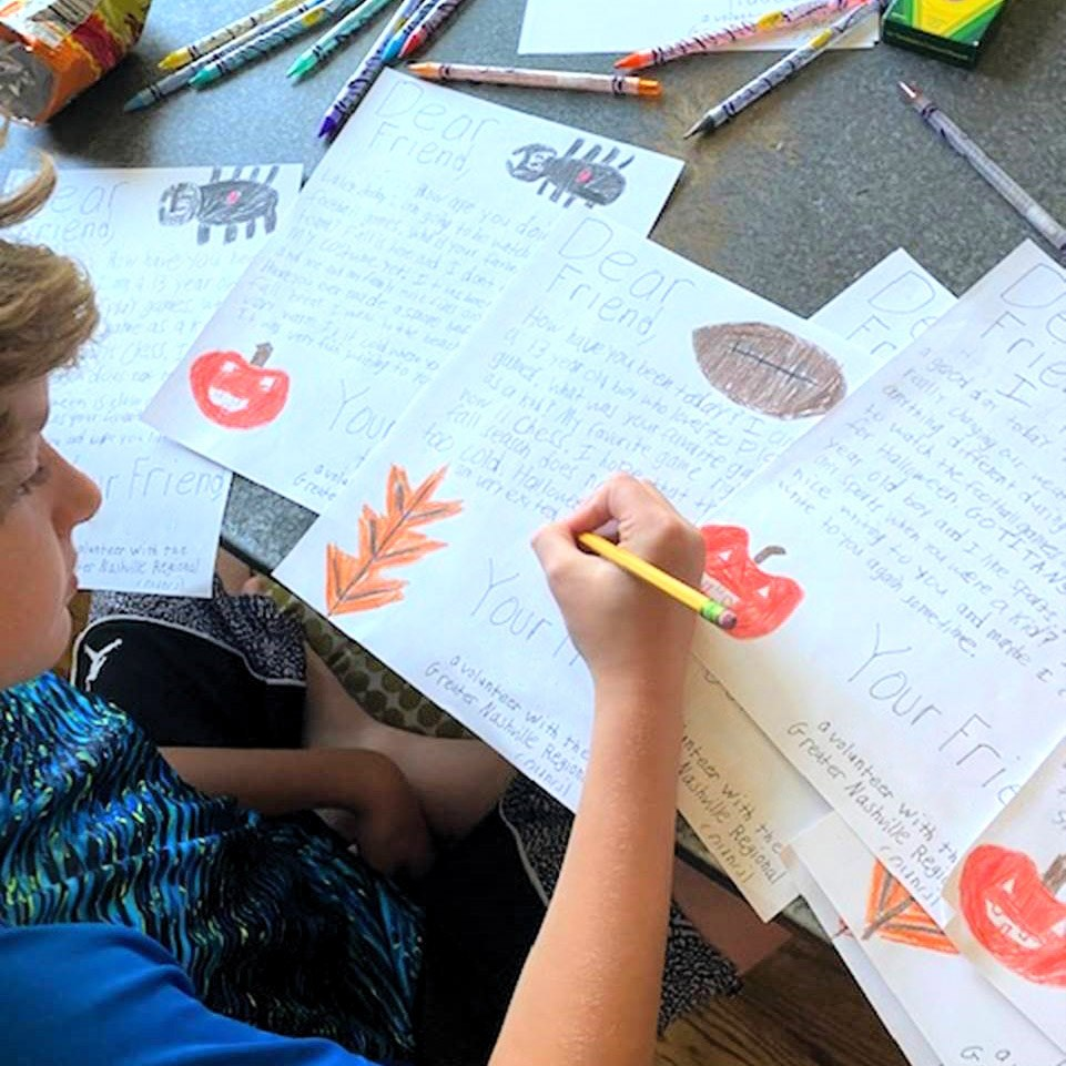 A child writes letters for seniors and those in assisted living communities.